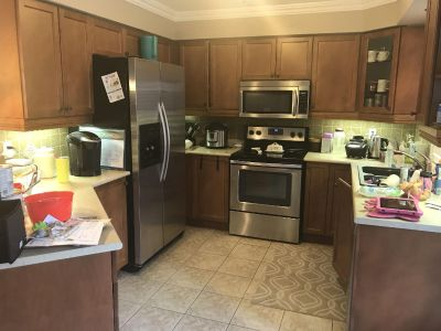 Kitchen cupboards, counter top, sink & faucet.