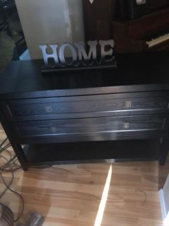 Lovely, solid, black TV or Entry tell o table. 4 Long by 22 deep by 34 tall. Has two drawers, nice top and open shelf on the bottom.