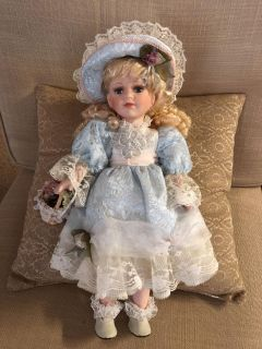 Porcelain doll with blonde hair and blue eyes - good condition