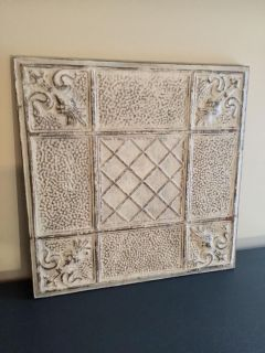 Antique rustic tin ceiling tile mounted on wood.