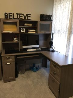 Gray L-Shaped desk with hutch and file cabinet.