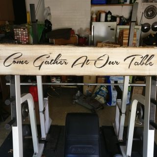 wooden sign says come gather at the table