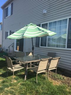 Glass patio table with umbrella and 6 chairs