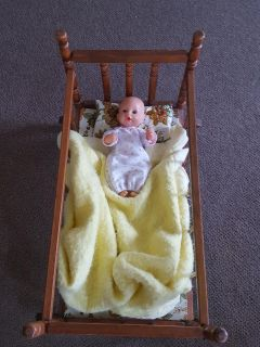 Baby doll in wood cradle crib with accessories