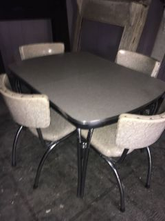 1950 s Formica and chrome dinette set with four chairs. One chair has some clear tape repair to it.
