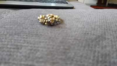 Gold colored ring with a rose on it