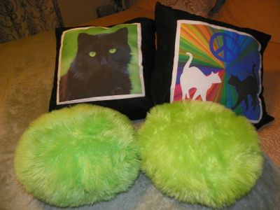 2 cat pillows and 2 pom-pom pillows.
