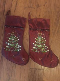 2 burgundy Christmas stockings. Small bells at top and ribbon detail on trees.
