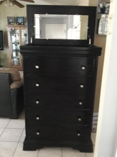 Black dresser with attached mirror and compartment space