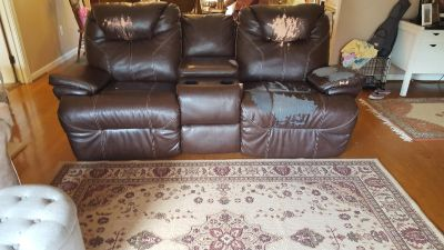 Reclining leather sofa with storage and 2 cup holders.