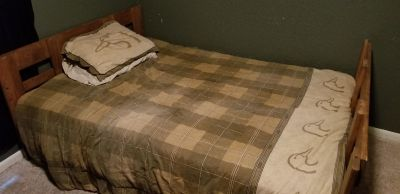Full size wood bed with mattress and bedding