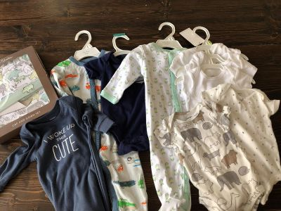 An assortment of 0-3 months onesies, sleep sets, and rompers for boys.