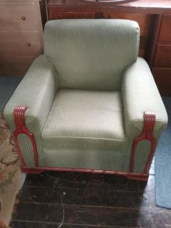 Comfortable green chair with wood trim