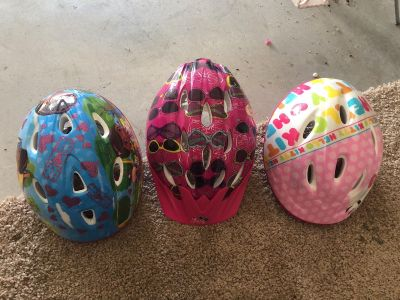 Two toddler helmets and one child helmet