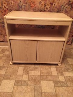 Tv stand with storage on rollers. Very sturdy.