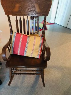 A wooden chair with two pillows