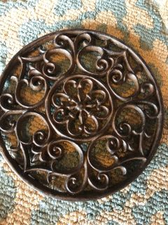 Heavy iron trivet or there s a hanger bracket on the back to hang on wall.