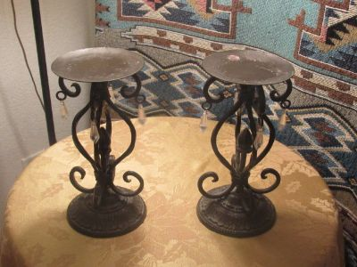2 Wrought iron candle holders have crystals hanging from them