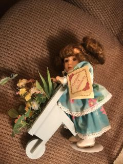 Porcelain doll with wheelbarrow of flowers and doll stand