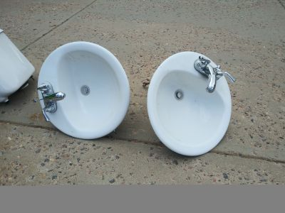 2 white bathroom sinks with Delta faucets