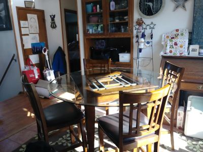 Round glass table with four chairs in great condition. Need something bigger.