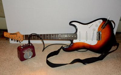 Electric guitar, strap, mini amp and cable