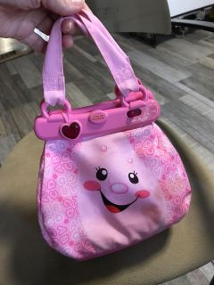 Fisher-Price singing and talking purse. Needs new batteries and has a stain that I did not try to get out