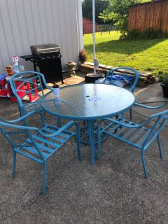 Patio table and chairs and umbrella stand