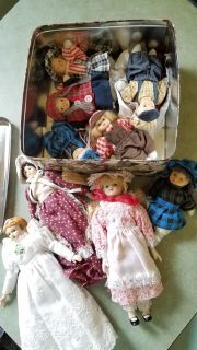 Tin of small porcelain dolls