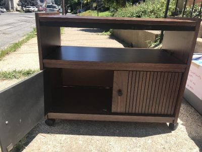 Rolling TV stand with pull out shelf and cabinet.