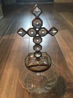Glass jar with cross on top.