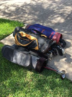 Three golf bags and various clubs