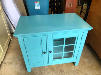 Blue media cabinet with shelves inside both doors