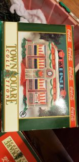 SEVEN CHRISTMAS COKE BUILDINGS FROM THE TOWN SQUARE COLLECTION AND 9 PIECES OF VILLAGE PIECES ALL 1992-1994
