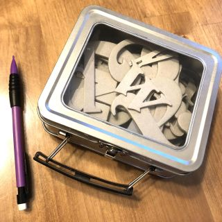 Tin filled with chipboard letters