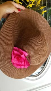 Brown summer hat with pink flower attched.