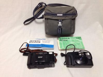 Two vintage cameras with case. Chinon has tape on battery compartment. Chinon Trle Wide 35 FX-Tm. Canon Strappy LX. No way to test.