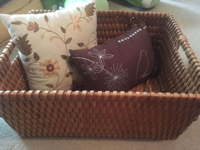 Large wicker basket and pillows with embroidery