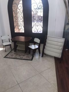 Little kids table with chairs and bookcase.