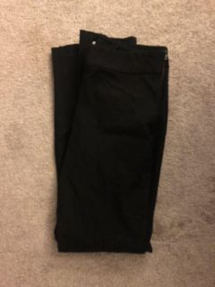 Black professional dress pants with gold zipper on hip