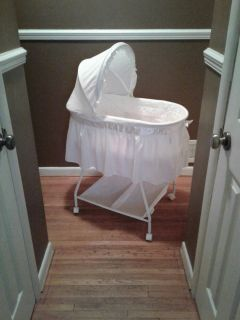 White bassinet with canopy and mattress