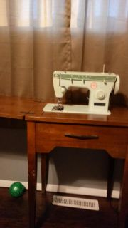 Older antique Singer sewing machine in table