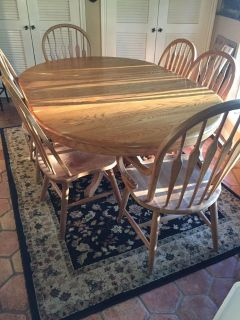 Oak Pedestal Table with 10 chairs. Two Captain Chairs. Picture shows leaf with table.