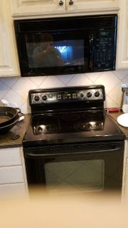 GE Electic Range with Microwave mounted above stove.