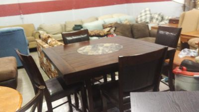 Solid dark wood 4ft X 4ft table with a lazy Susan built in the Middle with four chairs an excellent shape