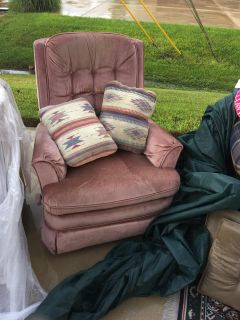 Soft rose colored rocker recliner with pillows