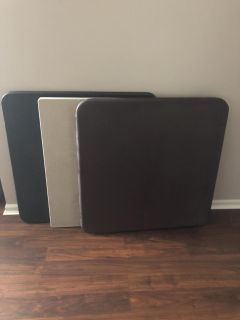 Three square foldable tables . Brown , black and a plastic grey