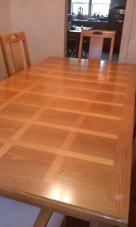 inlaid oak dining table with cushioned chairs