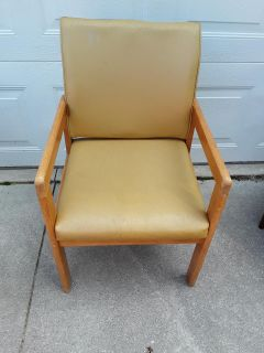 Wood / gold color vinyl material on chair and back. No holes in fabric. Great solid confortable chair