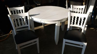 Round white table with leaf. 4 chairs black cushions